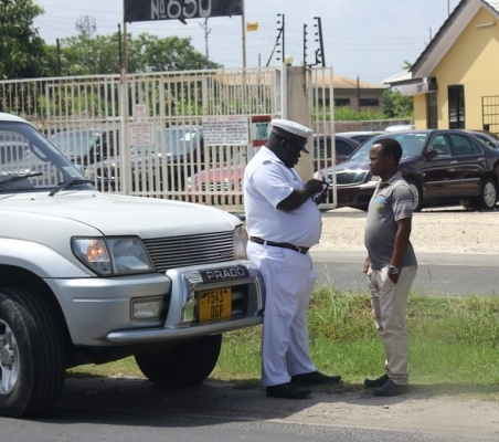 A traffic police officer writes out a traffic offence notification for a motorist along Ali Hassan Mwinyi Road in Dar es Salaam yesterday. Photo: Halima Kambi