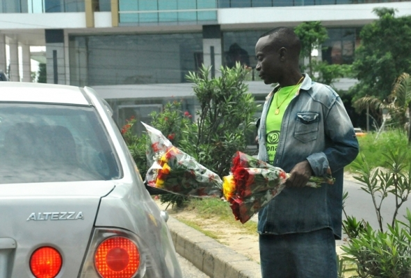 Flowers vendor display their merchandise to car passengers to buy it at traffic lights of the Ali Hassan Mwinyi and Haile Sellasie Roads at Oysterbay St. Peters Church area in Dar es Salaam yesterday. Photo: John Badi