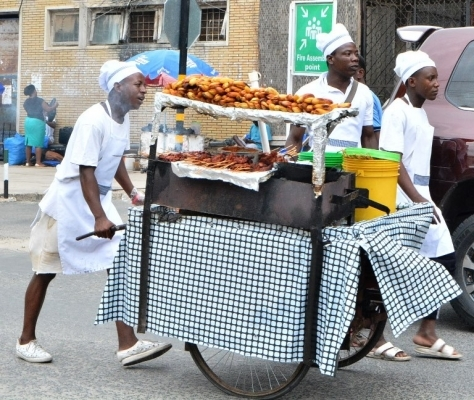 Foods vendors negotiate way while display their merchandise looking for potential customers along Pamba Street in the city centre of Dar es Salaam yesterday. Photo: Correspondent Miraji Msala