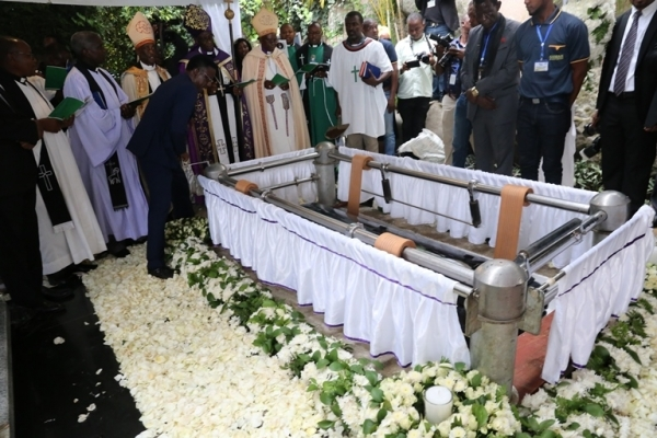 The casket bearing the remains of Dr Mengi is lowered into the grave by special device during the burial ceremony. Photo: Selemani Mpochi