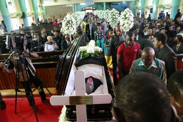 Mourners pay their last respects before the body of Dr. Mengi.