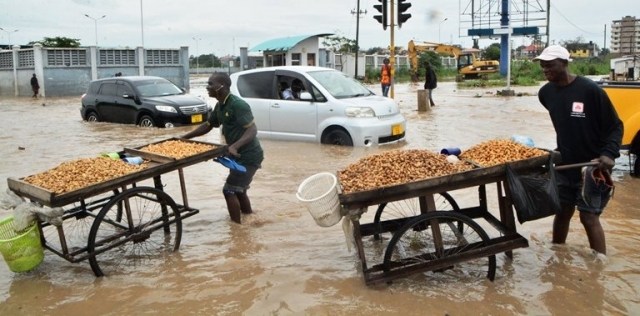 Boiled groundnuts vendors and motorcycle riders negotiate their way on a flooded section along Morogoro Road at Jangwani area following heavy rains in the city yesterday. Photo: Correspondent Miraji Msala