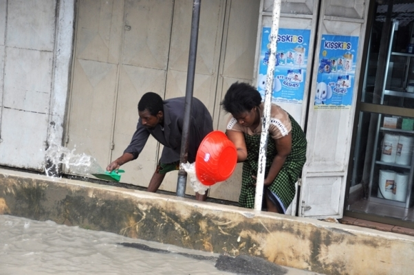 Tandale kwa Mtogole residents remove water from a house following heavy rains yesterday. Photo: John Badi