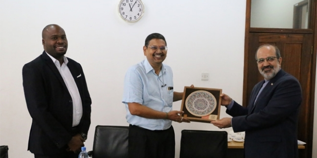 Ambassador Farhang (R) presents a souvenir to The Guardian Limited general manager Chintaruri, as human resources manager Emmanuel Matondo looks on.